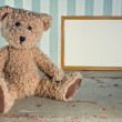 Antique teddy bear sitting next to an empty wooden frame — Stock Photo #18021023