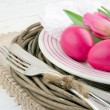 Easter dinner setting with two pink eggs and tulip - Stock Photo