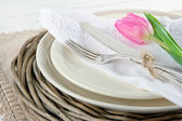 Pink tulip on rustic dinner setting — Stock Photo