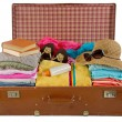 Old vintage suitcase packed with clothes - Stock Photo