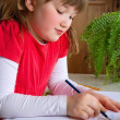 Little girl drawing at her desk — Stock Photo