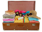 Old vintage suitcase packed with clothes — Stock Photo