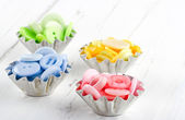 Pastel color buttons in old metal cupcakes — Stock Photo