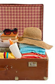 Vintage suitcase packed with clothes for beach vacation — Stock Photo