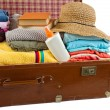 Old vintage suitcase packed with clothes and vacation accessorie — Stock Photo #21641367