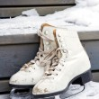 Pair of old white skates on snowy stairs — Stock Photo