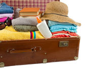Old vintage suitcase packed with clothes and vacation accessorie — Stock Photo