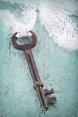 Old metal key with romantic white lace — Stock Photo