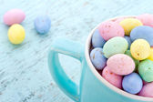 Small pastel easter eggs in a blue cup — Stockfoto
