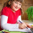 Stock Photo: Smiling girl drawing at her desk