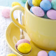 Easter eggs in a yellow cup on wooden background — Stock Photo #22155749