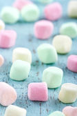 Colorful small marshmallows on wooden background — Stock Photo
