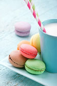 Pastel color macaroons and a cup of milk — Stock Photo