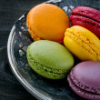 Macaroons on dark wooden background — Stock Photo