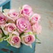 Roses in an old blue wooden basket — Stock Photo