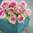Stock Photo: Roses in an old blue wooden gardening basket