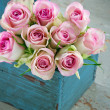 Roses in an old blue wooden gardening basket — Stock Photo