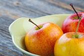 Läckra äpplen i en gul skål — Stockfoto