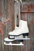 Old figure ice skates on a rustic wooden wall — Stock Photo