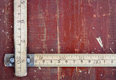 Old meter stick on old wooden background — Stockfoto