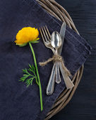 Rustic dinner setting with with a yellow flower — Stock Photo