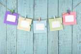 Five empty photo frames hanging with clothespins — Stock Photo