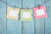 Three empty photo frames hanging with clothespins — Stock Photo