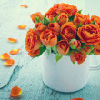Vintage edited orange roses in a white cup — Stock Photo