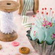 Handmade pincushion on floral fabric background — Stock Photo