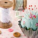 Handmade pincushion on floral fabric background — Stock Photo