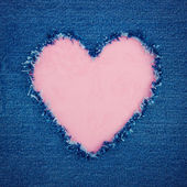 Pink vintage heart on blue denim fabric — Stock Photo