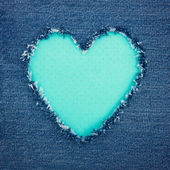 Turquoise vintage heart on blue denim fabric — Stock Photo