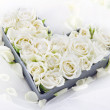 Heart shaped tray full of white wedding roses — Stock Photo