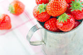 Strawberries in an old metal measurement cup — Stock Photo
