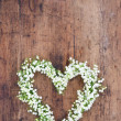 Heart shaped flower wreath on rustic background — Photo