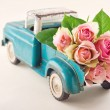 Antique toy truck carrying pink roses — Stock Photo