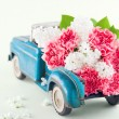 Toy truck carrying pink carnation and lilacs flowers — Stock Photo #32149295
