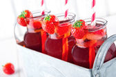 Glasses of red strawberry juice with frozen icecubes — Stock Photo