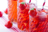 Glasses of red strawberry juice on vintage towel — Stock Photo