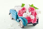 Toy truck carrying pink carnation and lilacs flowers — Stock Photo
