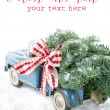 Blue toy truck carrying a Christmas tree on white background — Foto de Stock