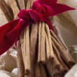 Cinnamon sticks tied with a red ribbon in wrapped paper — Stock Photo