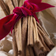 Cinnamon sticks tied with a red ribbon in wrapped paper — Stock Photo #37008927