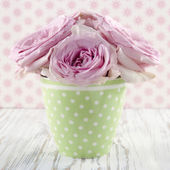 Pink flowers in a green polkadot vase — Stock Photo