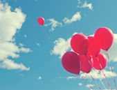 Bunch of red ballons on a blue sky — Stock Photo