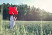 Girl with a bunch of red balloons — Stock Photo