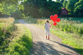 Little girl with a bunch of red balloons — Stock Photo