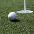 Golf ball and hole on a field - Stock Photo