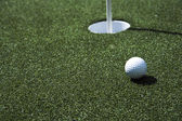 Golf ball and hole on a field — Stock Photo