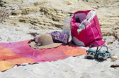 Straw hat, bag, towel and flip flops on a beach — Stockfoto